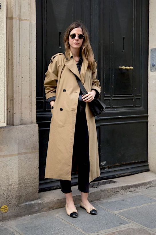 Classic Trench Coat Outfit for Spring — Round sunglasses, black crossbody bag, black raw-hem jeans, and Chanel cap-toe flats.