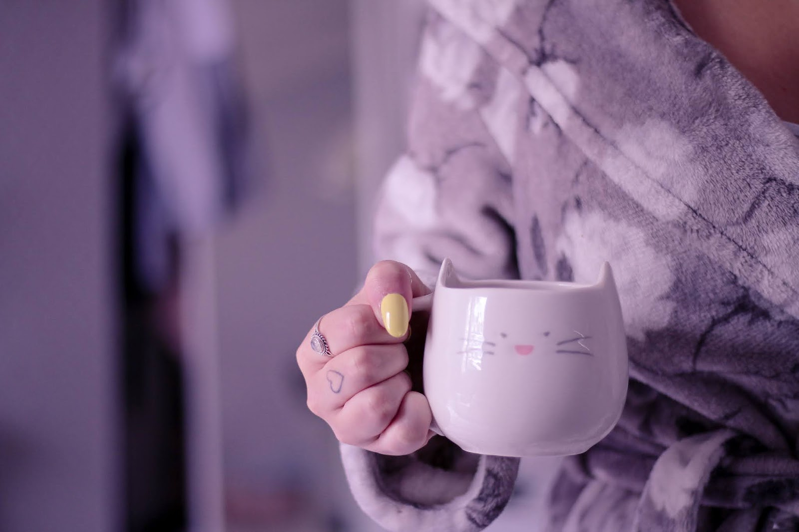 Medium close up shot of a girl in a grey robe holding a white cat mug