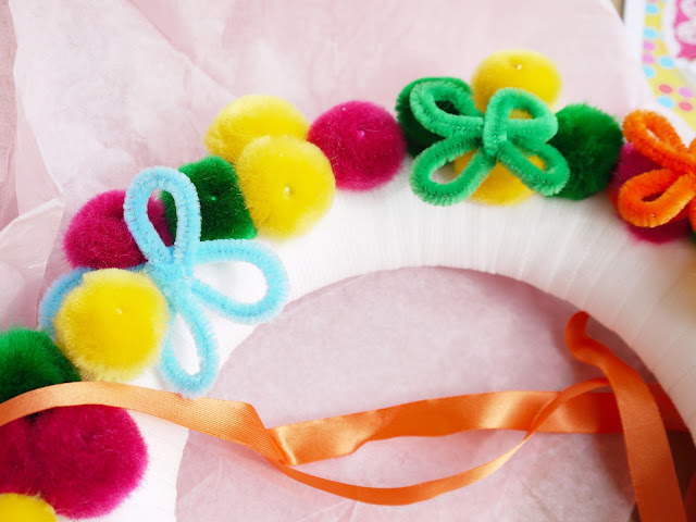 closer detail of the pink, green, and yellow pom poms and blue and green pipe cleaner flowers on the wreath