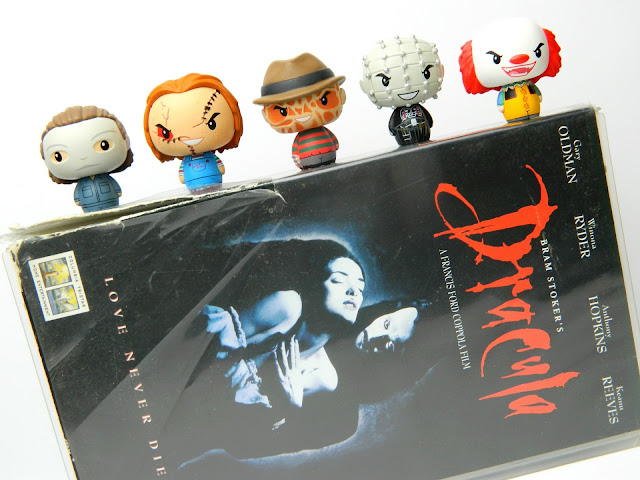 A photo showing a VHS tape of the horror movie Dracula, with horror character figures sitting on top