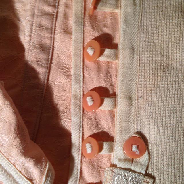 Praktikus, hogy a gombok pamut textil szalagra vannak fűzve. Jobb és bal oldalon illetve középen gumiszállal szőtt pamut betét biztosítja a komfortosan elasztikus (strech) viseletet.