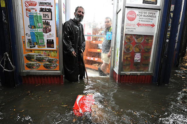 A vagrant stands in the entryway of a shop during streak flooding brought about by Ida.   Anthony Behar/Sipa USA