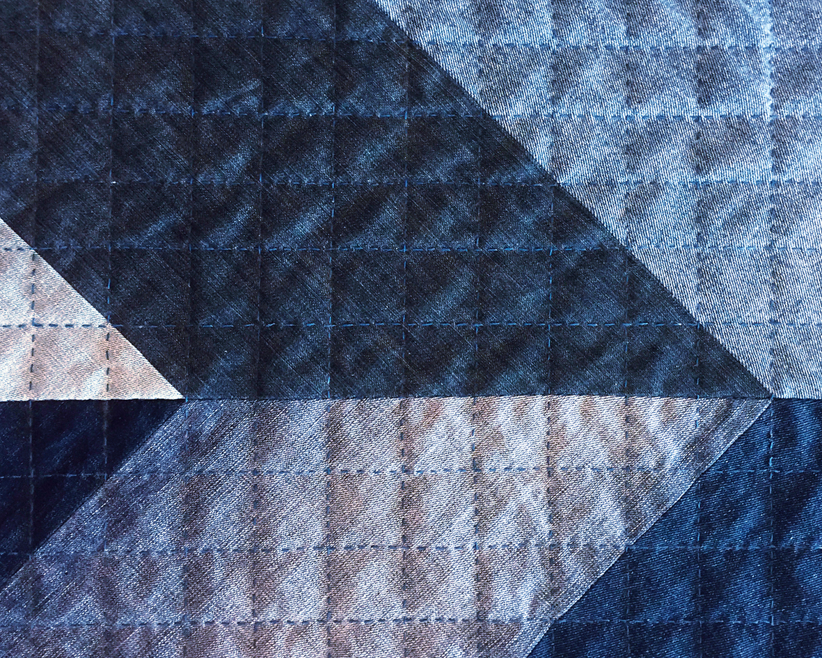 Close up of hand quilting on a denim quilt