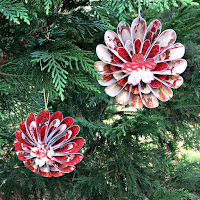 two 3D circular paper ornaments hanging on evergreen tree