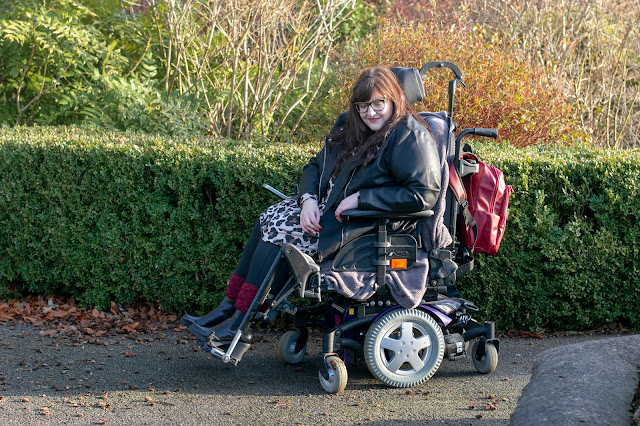 Plus size woman sat side on in powerchair with red backpack on the back of chair