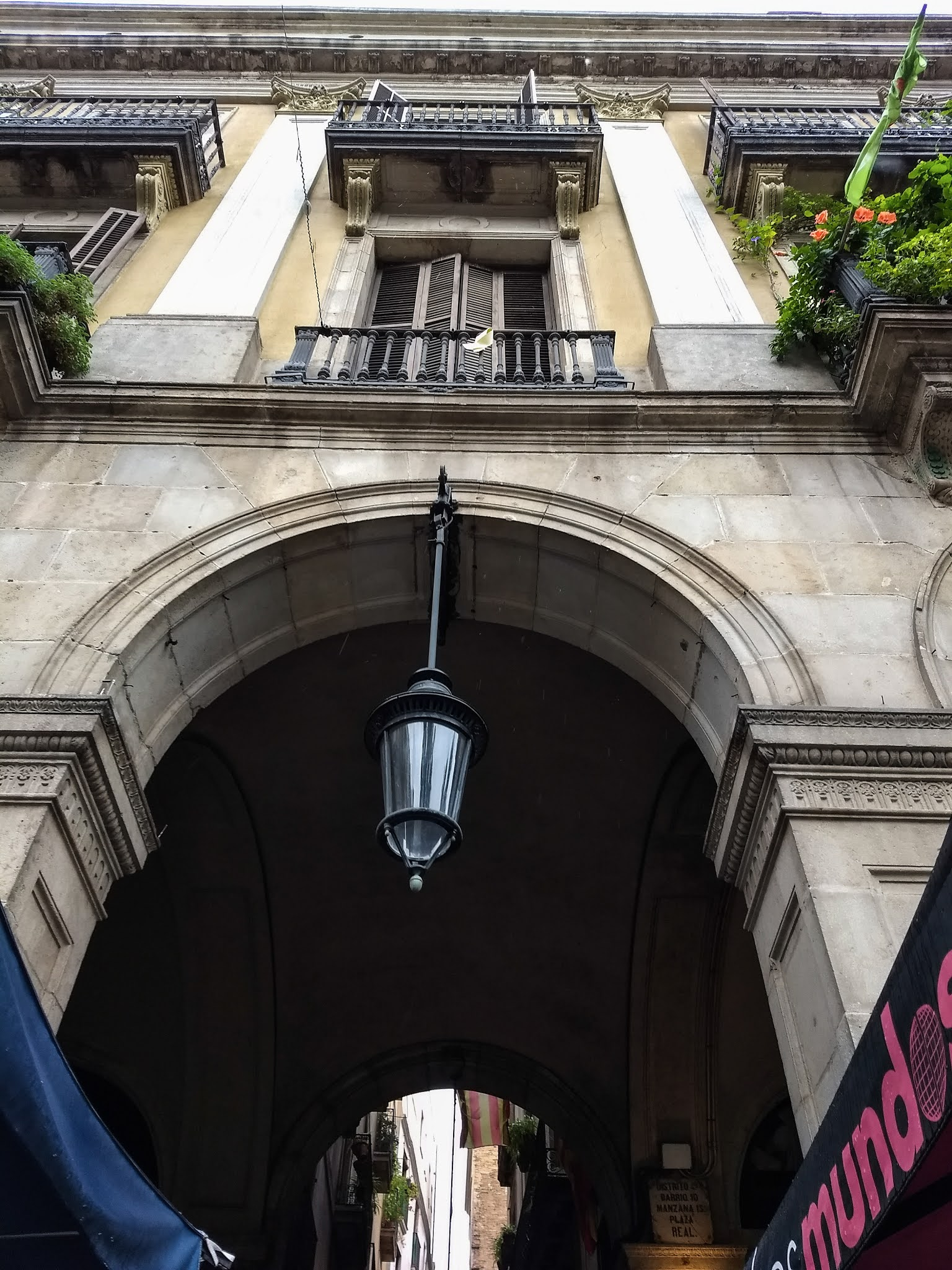 Looking up at an archway with a hanging light and balconies above on Plaza Reial in Barcelona.