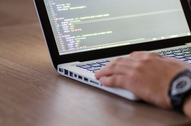seorang pria dengan beberapa kode program dilaptopnya