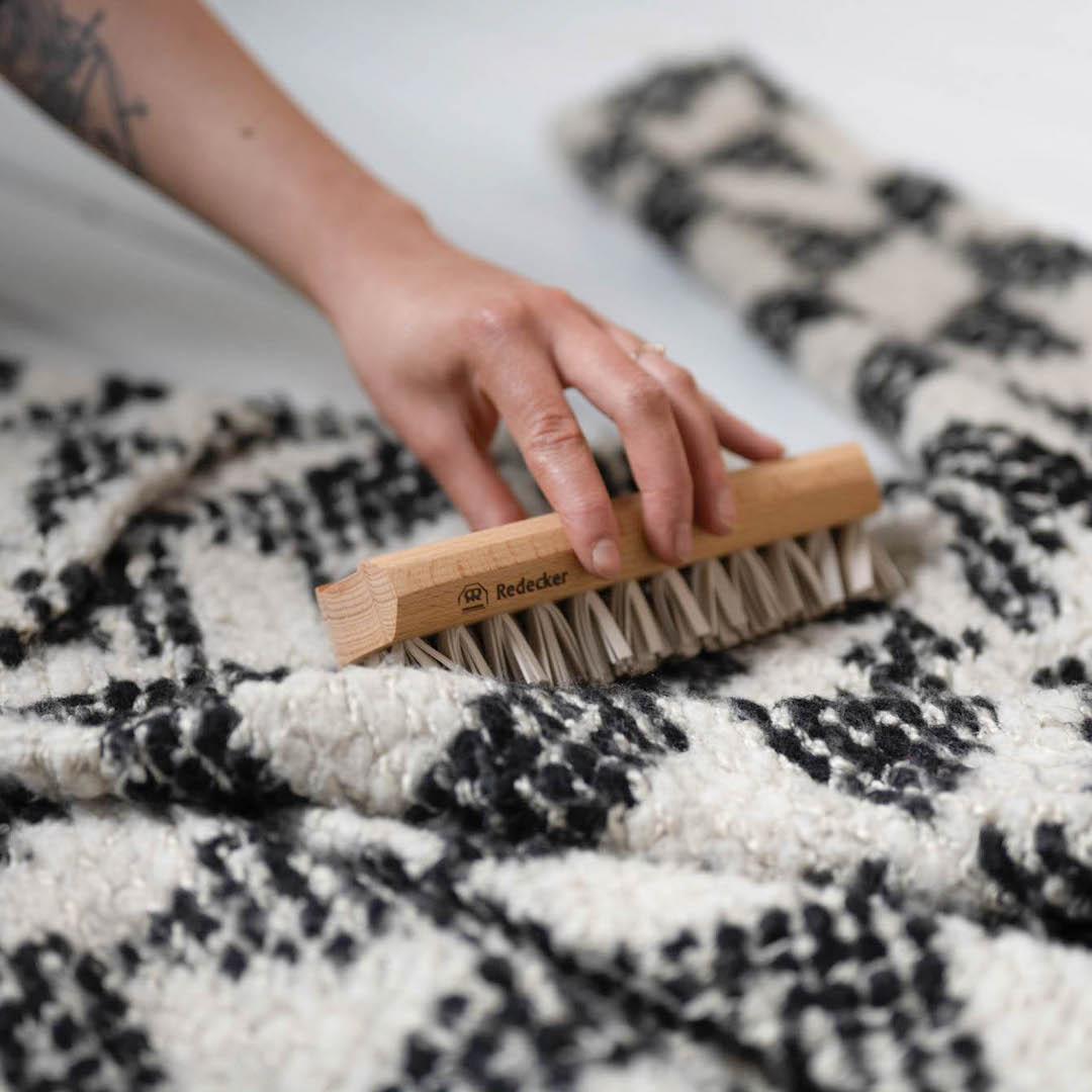 Valkoisella lattialla musta-valkea villakangastakki jota ihminen puhdistaa harjaten takkia nukkaharjalla