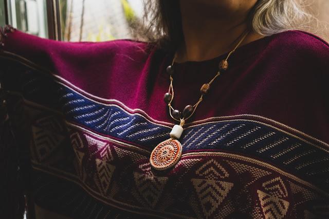 mulher usando colar de cerâmica com poncho