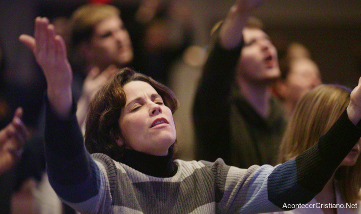 Mujer orando con manos levantadas en iglesia