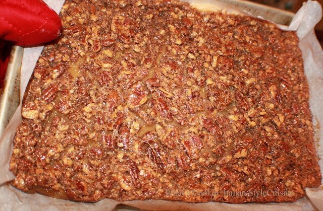 these are baked pecan pie bars on a white plate with loads of pecans in a rich topping