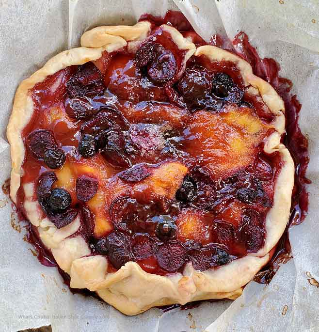 this is a fruit galette with peaches, blueberries and bing cherries