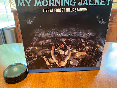 "Photo of a puzzle box that has a picture of a band from the back of a stage. It says ""My Morning Jacket."""