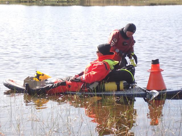 Henkilö istuu pelastautumispuvussa SUP-laudalla, lastattuna sukellusvarusteet ja vesikiikari, kuivapukuinen henkilö taustalla