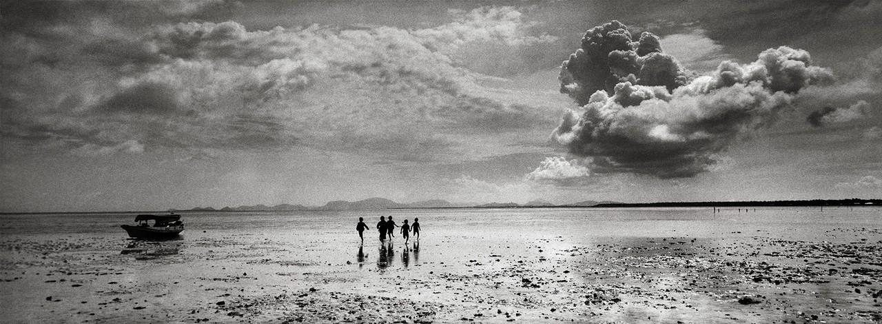 Photo panoramique de Pierre de Vallombreuse d'enfants Badjaos sur une plage