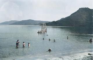 Orang orang yang sedang menikmati pantai danau toba