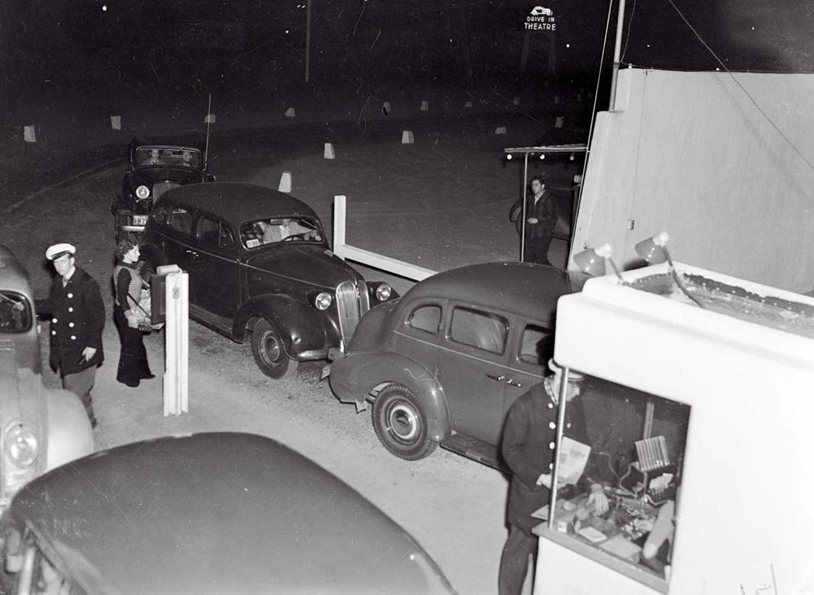 "(Original Caption) The Cinemotor Theater. Los Angeles, Calif.: Motoring and motion pictures achieve a happy wedding in the Drive-In Theater in Los Angeles. The theater is a parking lot with graduated tiers from which motorists seated in their cars, watch the films projected on a giant screen. Synchronized amplifiers in the front of each car make speech audible in all parts of the lot. Here's the entrance to the unique theater, showing the cashier's wicket, and ""butcher-girl"" in front."