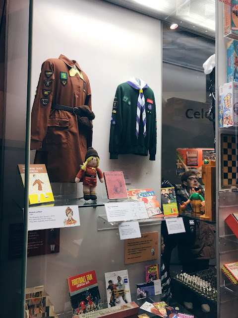 Display case showing brownie and scout uniforms