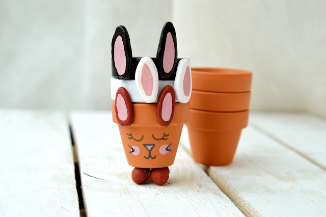 DIY Bunny Egg Cups made from mini planters by Motte's blog, stacked into a pile