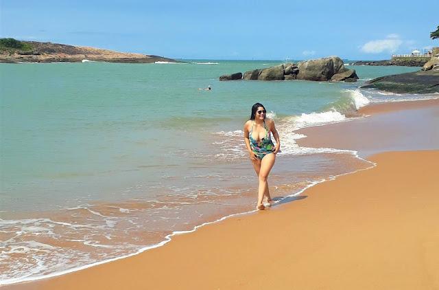 mulher de biquini verde andando na areia da praia