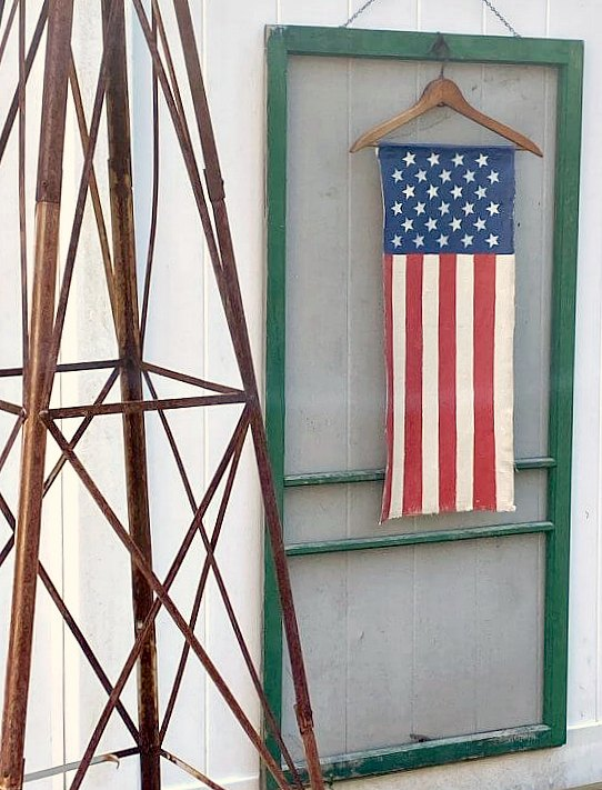 Vertical American flag hanging on a vintage green screen door