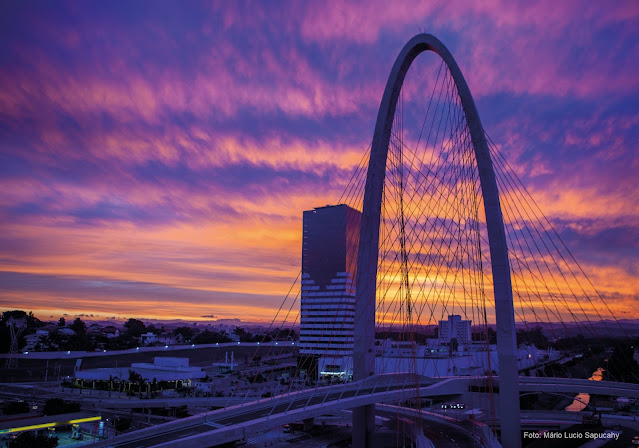Pôr do sol em tons de violeta e rosa, em cena urbana com ponte estaiada