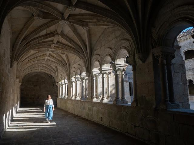 Mujer paseando por claustro medieval