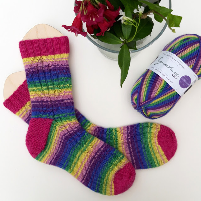 Flatlay of a pair of socks in Wildflower and pink yarn.  The socks are on wooden blockers. There is a vase of flowers to the top of the picture and a ball of Wildflower yarn to the right