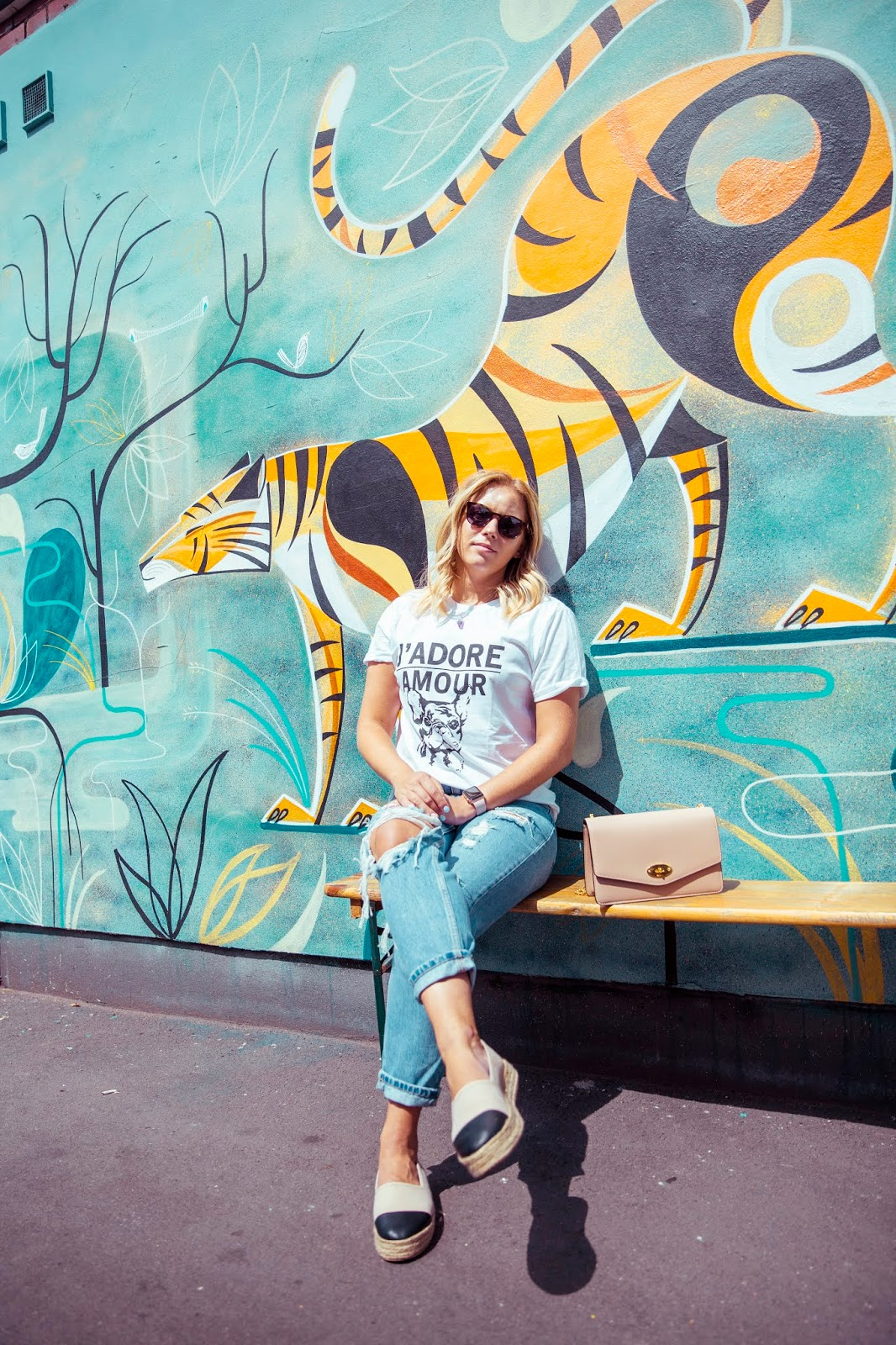 Rachel Emily sat under a tiger mural on North Street, Bedminster, Bristol in casual jeans and a t-shirt