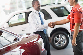 A salesman shakes hands with a customer at a car dealership.