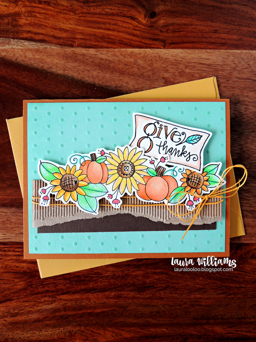 This is a handmade fall card with an aqua background. The focal point is a spray of sunflowers and pumpkins, with greenery. It was colored in warm colors with colored pencils. There is a notched tag that says Give Thanks, tucked into the plants. The sunflowers and pumpkins are resting on a strip of Kraft colored corrugated stock, and dark brown cardstock, wrapped with yellow twine. The stamps are from Impression Obsession. The card is resting on a yellow envelope, on a dark brown woodgrain surface.