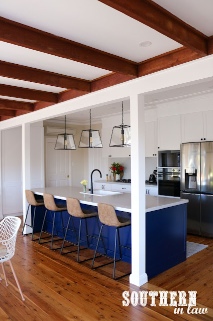 Hamptons Shaker Kitchen with Navy Blue Island, Wood Floors, White Cabinets, Black Handles and Grey Stone Benchtop