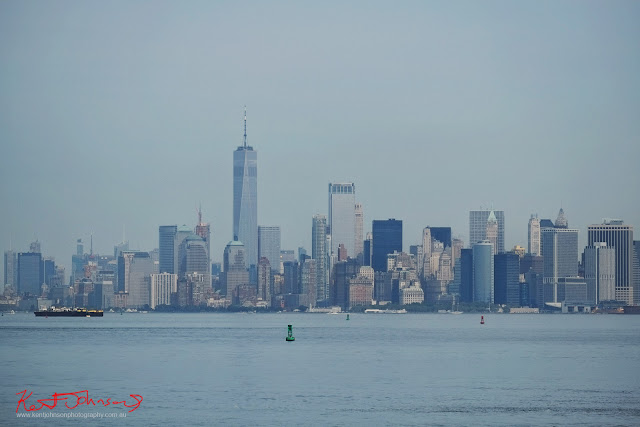 A hazy view of the Manhattan skyline and shipping buoys photographed from the Staten Island Ferry on Manhattan Harbor.  Travel photography by Kent Johnson.