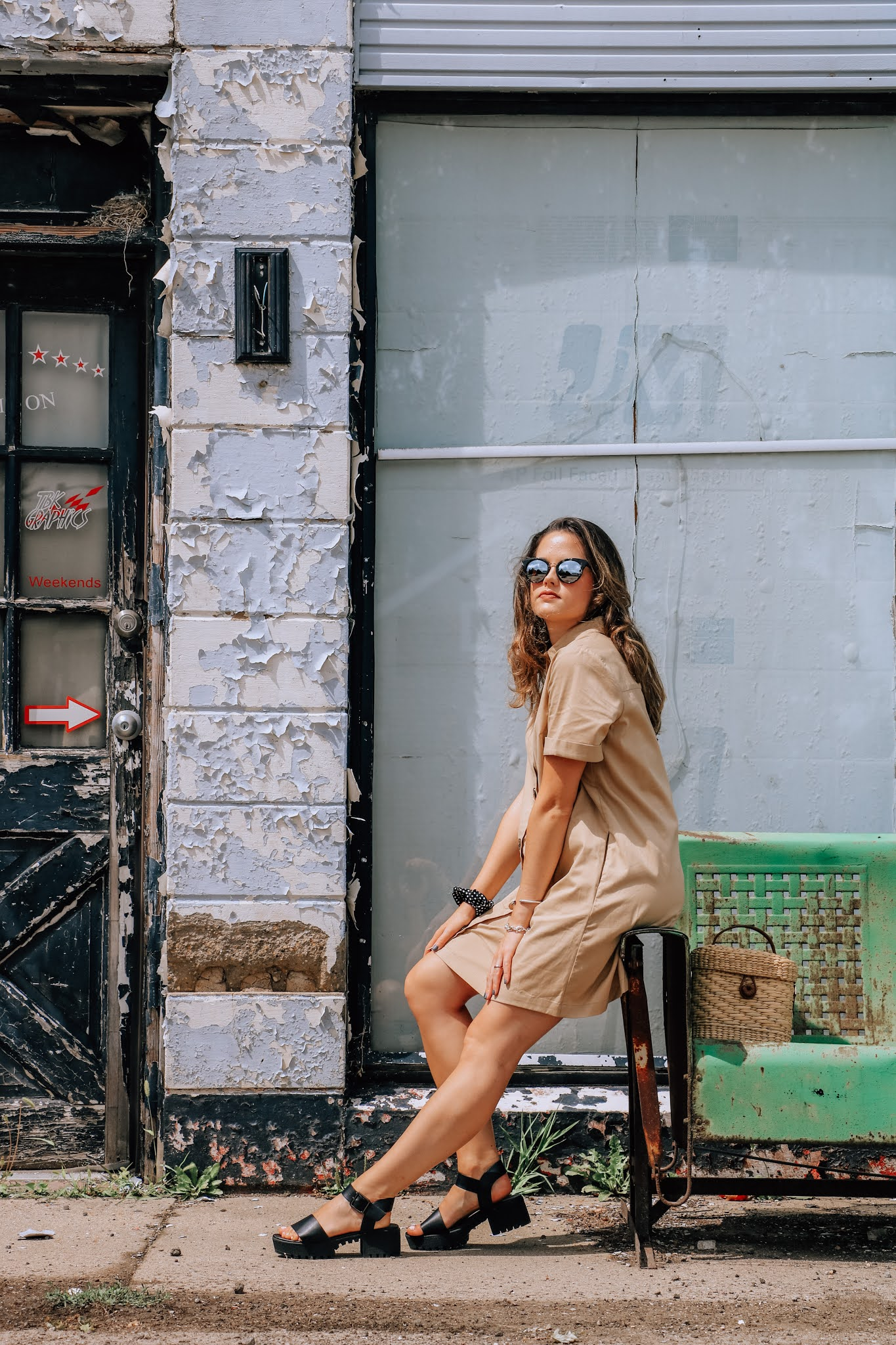 Fashion blogger Kathleen Harper doing an outdoor photo shoot at a bus stop in fall 2020.
