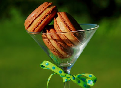 chocolate macracons with a peanut butter filling stacked in a martini glass
