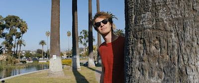 Movie still for A24's latest film Under the Silver Lake where Andrew Garfield looks sneakily from behind a palm tree with his sunglasses on