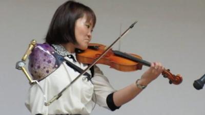 فتاة يابانية لا تعرف المستحيل مانامي تعزف على آلة الكمان بيد إصطناعية