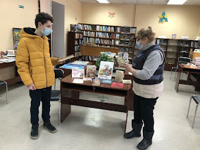 Читатель и библиотекарь возле выставки фото
