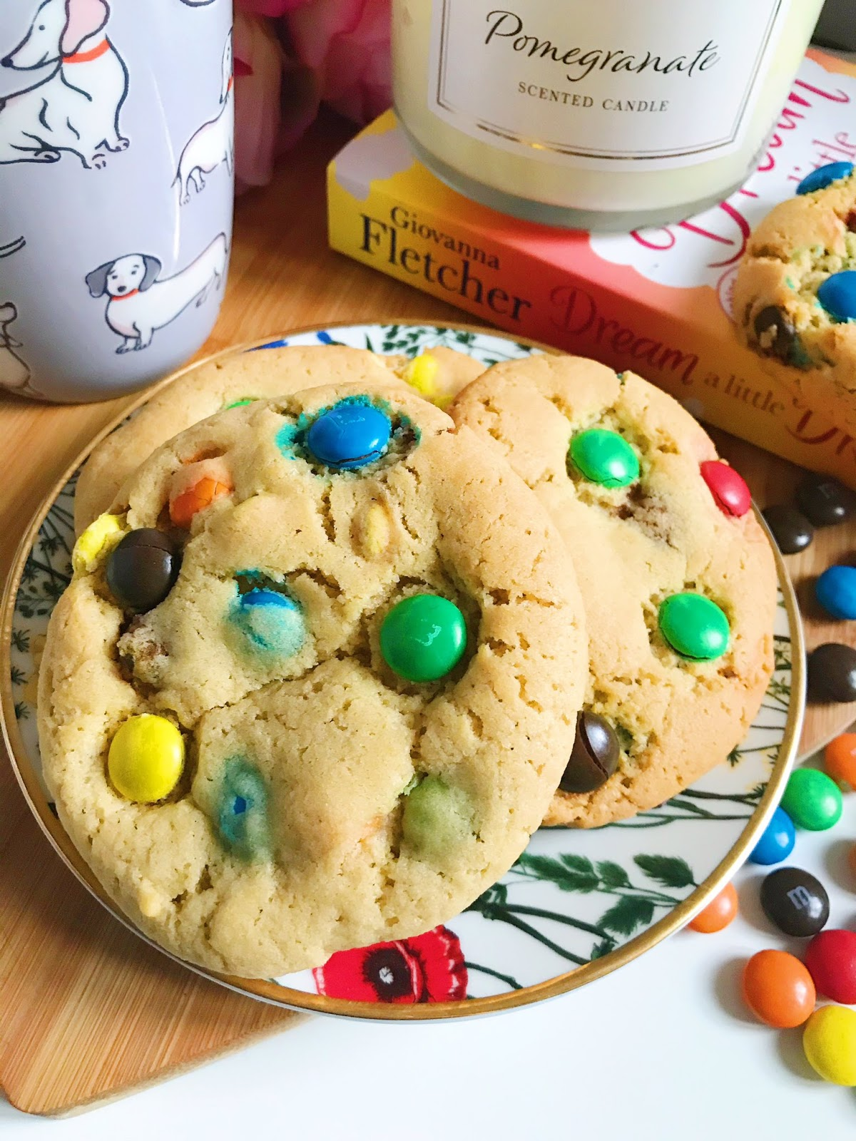 M&M cookies on a flower trinket dish on heart chopping board, cath kidston mug to the left, book to the right with candle on top