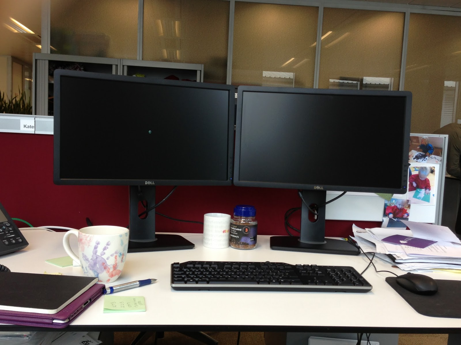 A desk in an open plan office with two monitors, phone and other desk stuff