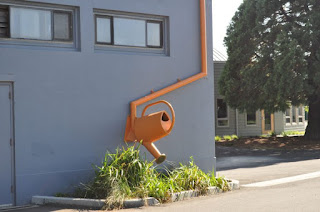 A orange rain spout in the shape of a giant watering can against a grey wall. In Anacortes, WA by Joe Mahl