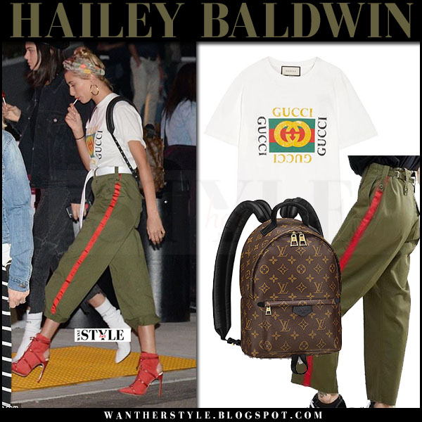 Hailey Baldwin in white logo print gucci t-shirt, green asos pants and red shoes what she wore april 2017