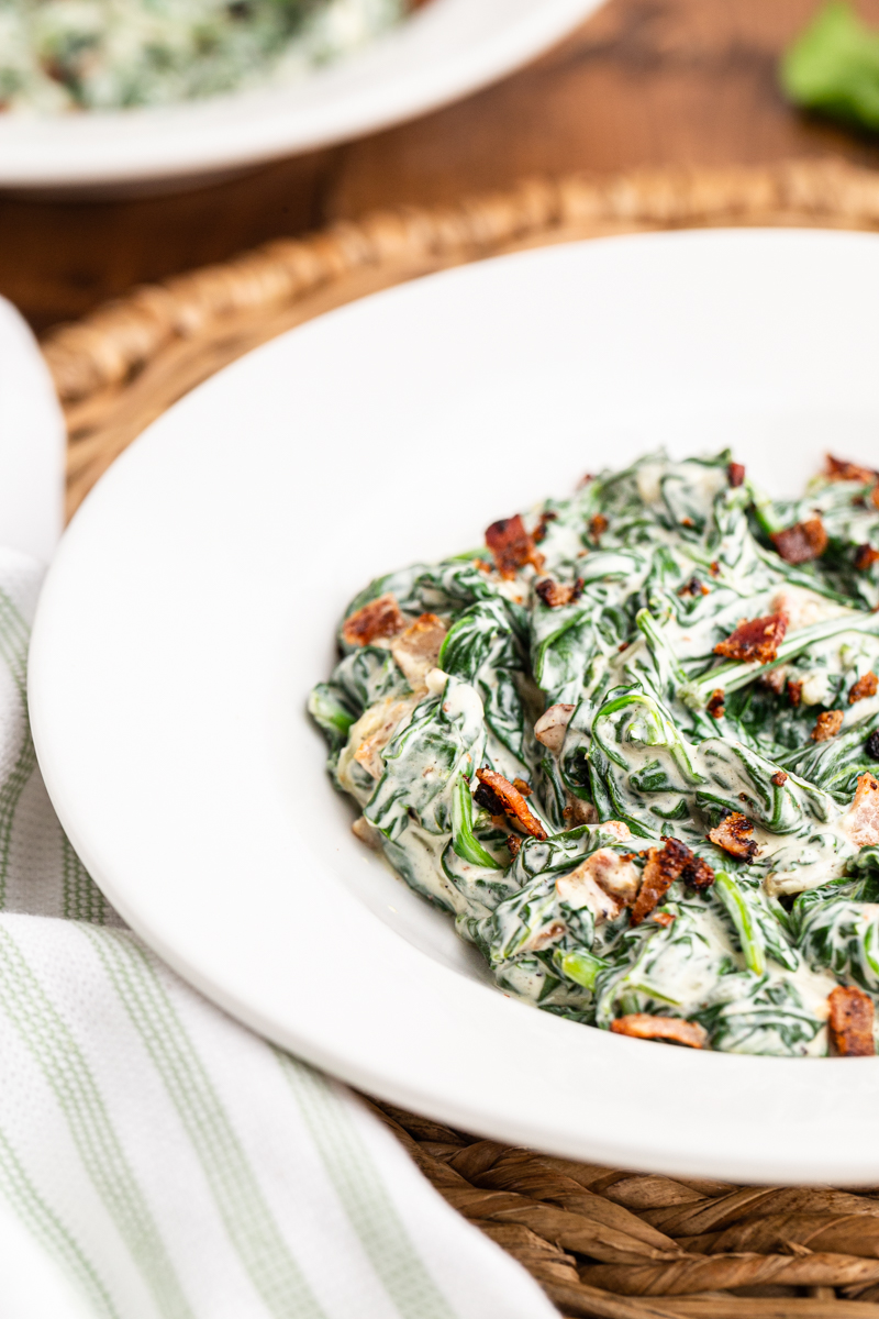 Closeup photo of a serving of Easy Creamed Spinach in a white bowl on a wooden table.