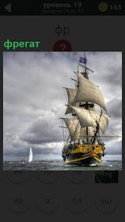 На море под облаками под всеми парусами двигается фрегат