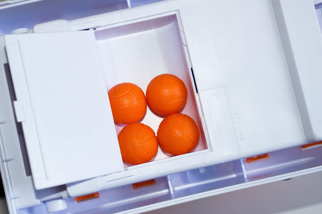 Close up photo of compartment in the bottom of the Little Tikes Hot Hoops game where the little plastic basketballs are kept