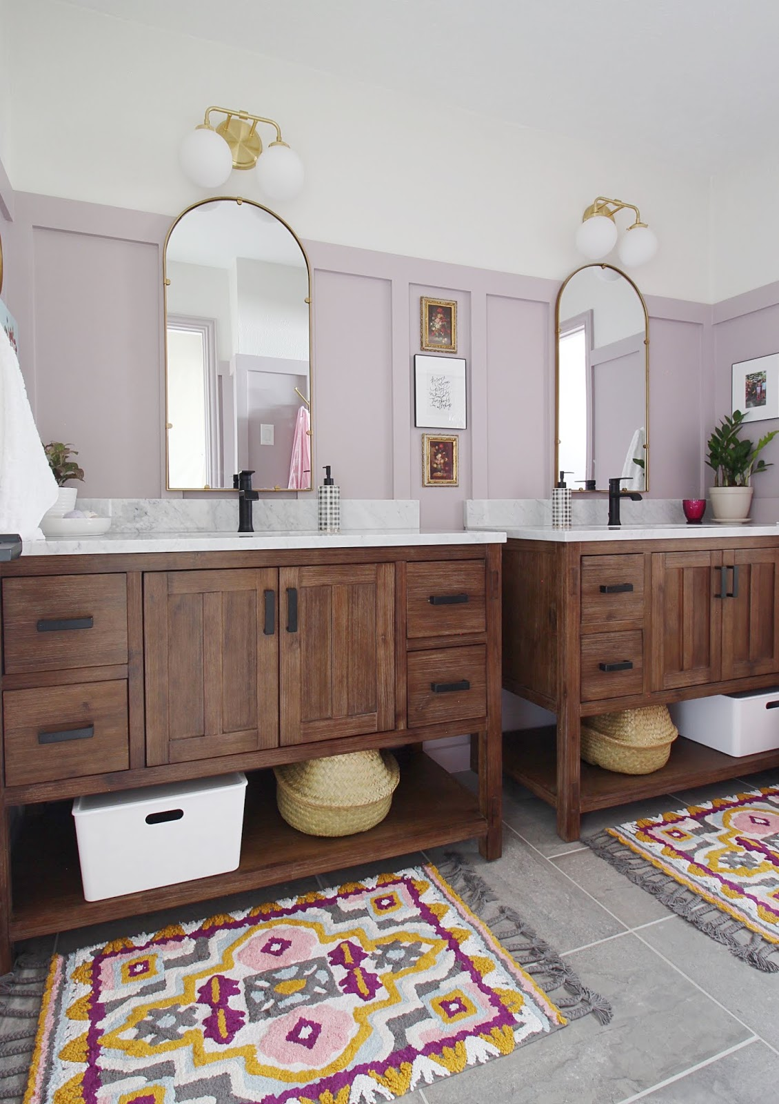 Side by side vanities, arched mirrors, brass and black fixtures, anthropologie bathmat rugs, basket weave floor tiles.