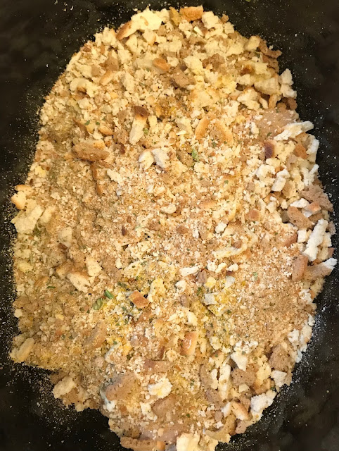 Slow cooker with chicken breast and stuffing mix on top.