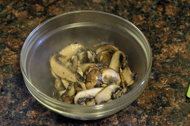 The fully cooked mushrooms in a bowl, on the counter.