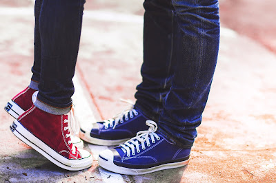 picture of a pair kissing, only their feet in sneakers visible