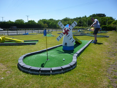 Playing the windmill hole on the Crazy Golf course at Penwith Pitch & Putt in Cornwall